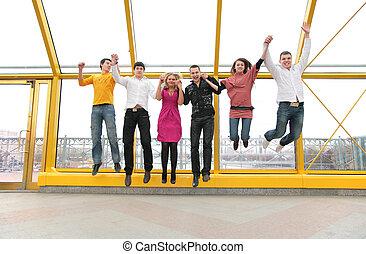grupo de personas jóvenes, salto, en, puente peatonal