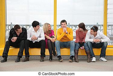 grupo de personas jóvenes, sentarse, en, puente peatonal