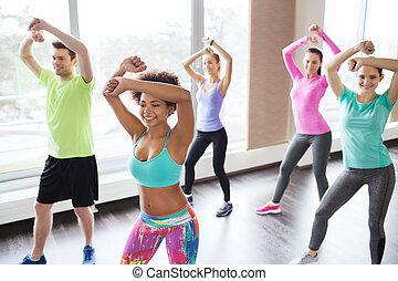 grupo, de, personas sonrientes, bailando, en, gimnasio, o, estudio