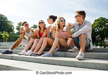 grupo, de, sonriente, amigos, sentado, en, ciudad, cuadrado