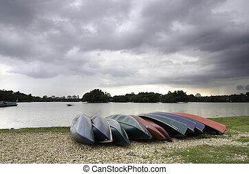 grupo, de, vacío, kayaques, en, el, orilla, de, el, lago, con, dramático, nubes