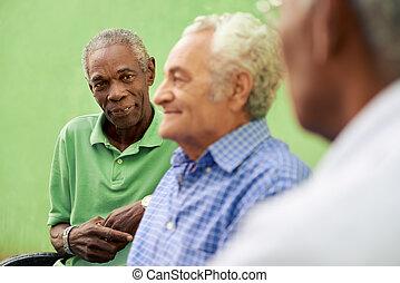 grupo, de, viejo, negro y, caucásico, hombres hablar, en el estacionamiento