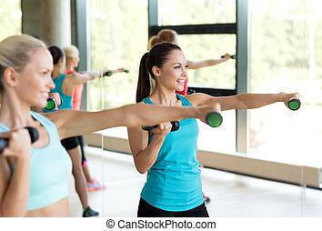 grupo mulheres, com, dumbbells, em, ginásio