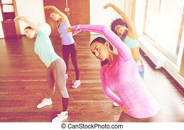 grupo mulheres, exercitar, e, esticar, em, ginásio