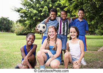 grupo multiétnico, de, feliz, macho, amigos, con, pelota del fútbol