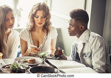 grupo multiracial, de, amigos, almorzar, juntos., dos, europeo, mujeres, y, uno, africano, tipo, en, café