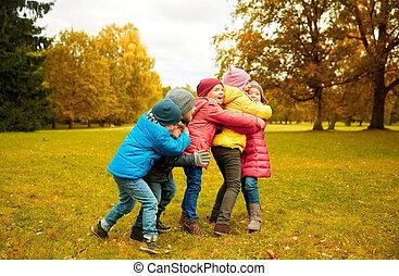 grupo, parque, abraçando, outono, crianças, feliz