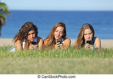 grupp, av, tre, tonåring, flickor, maskinskrivning, på, den, rörlig telefonera, lägga på gräset