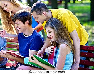grupp, student, med, anteckningsbok, på, bänk, outdoor.