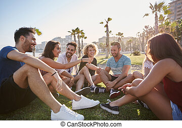 gruppe freunde, sitzen draußen, in, kreis, sprechende