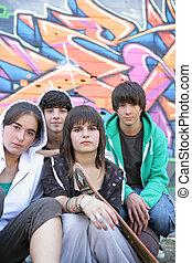 gruppe jugendliche, sitzen, vor, a, graffiti, wand