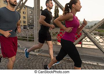 gruppe jungen leuten, jogging, über, der, brücke