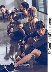 gruppe, von, athletische, junge leute, in, sportkleidung, sitzen boden, und, basierend, an, der, turnhalle, gruppe, fitness, begriff