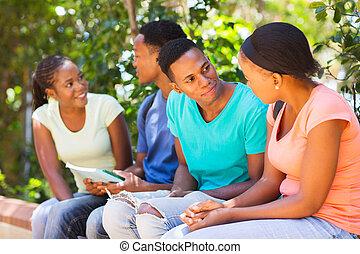gruppe, von, junger, hochschulstudenten, sitzen, draußen