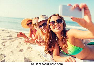 gruppe, von, lächeln, frauen, mit, smartphone, auf, sandstrand