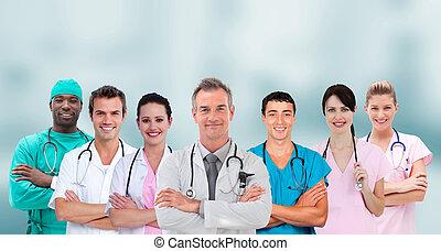 gruppo mescolato, di, medico, lavorante, standing, braccio attraversarono