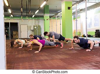 gruppo persone, fare push-ups, in, palestra