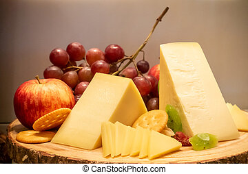 gruyere cheese with variety of fruit and cracker on wooden ...