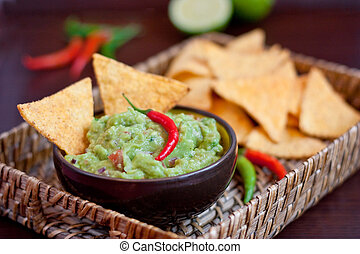 Guacamole and nachos with chili peppers