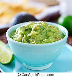 guacamole in colorful blue bowl with tortilla chips