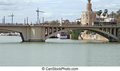 Seville city of Andalusia in Spain. Golden tower or Torre del Oro, a medieval military control tower on riverside of Seville. City sightseeing from Guadalquivir River Cruise.