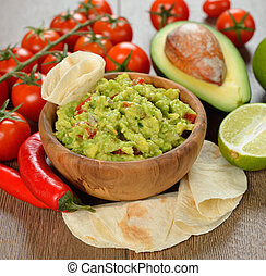 Guakamole and fresh vegetables on brown background
