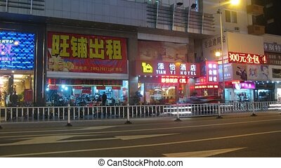 GUANGZHOU - NOV 21: (Timelapse View) Machines go at night on highway along shops and cafe, on Nov 21, 2011 in Guangzhou, Guangdong, China