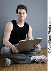 guapo, estudiante, joven, sentarse, trabajando, computador portatil