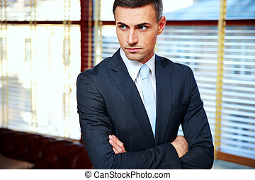 guapo, hombre de negocios, con, brazos doblados, en, oficina