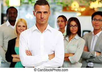 guapo, hombre de negocios, con, brazos doblados, posición, en frente, el suyo, colegas