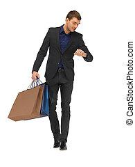 guapo, hombre, en, traje, con, bolsas de compras