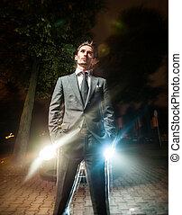 guapo, hombre, en, traje, posar, cerca, coche, por la noche