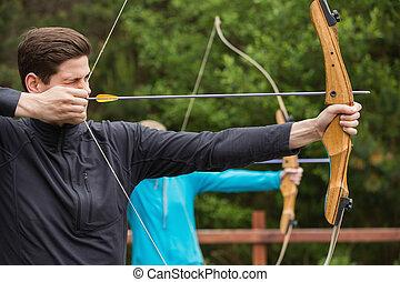 guapo, hombre, practicar, tiro al arco