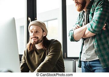 guapo, hombres, colegas, en, oficina, usar ordenador