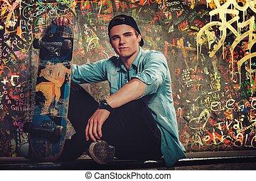 guapo, joven, con, monopatín, aire libre, contra, grafiti, pared pintada