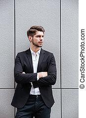 guapo, joven, posición empresario, con, manos doblaron