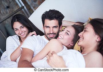 guapo, man en cama, con, tres, mujer hermosa