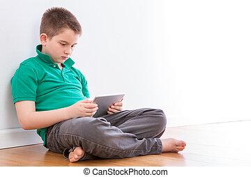 guapo, niño joven, con, tableta, reclinado, pared
