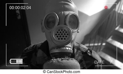 Guard dressed in military uniform in a gas mask looking in...