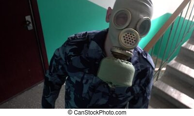 Guard dressed in military uniform in a gas mask threatened...