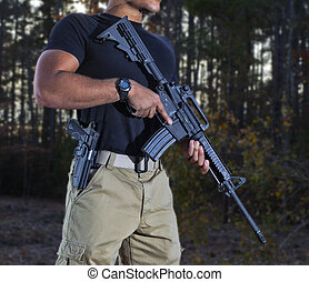 Civilian that looks like he is standing guard in the woods