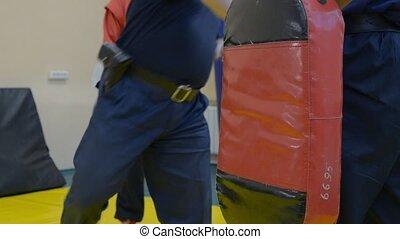 Guard hits punching bag by a leg
