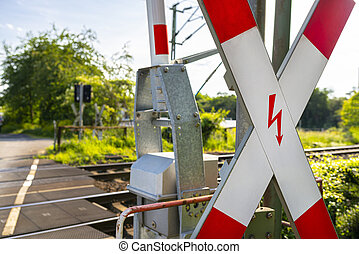 Guarded railroad crossing in the countryside with open barriers and cross of Saint Andrew.