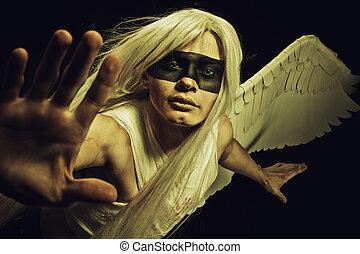 Handsome one-winged angel posing over dark background