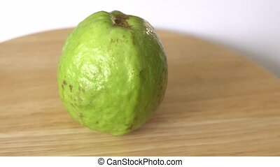 Guava rotates on wooden table and white background.