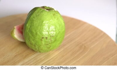 Guava with slice rotates on wooden table and white...