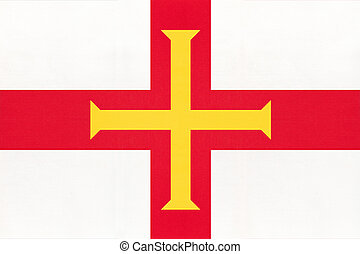 Guernsey island national fabric flag with emblem, textile background.