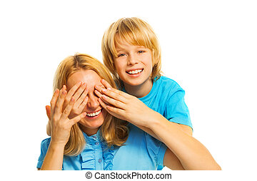 Little blond boy surprises his mom by covering her face with palms