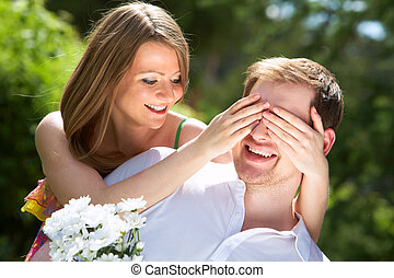 Guess who? - Photo of happy girl closing her boyfriend eyes...