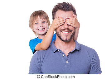 Guess who! Playful little boy covering his father eyes with ...